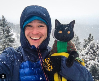 man and his black cat camping in the snow