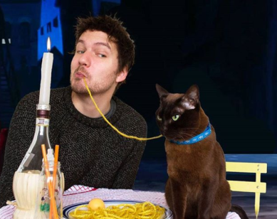 man and black cat share a string of spaghetti